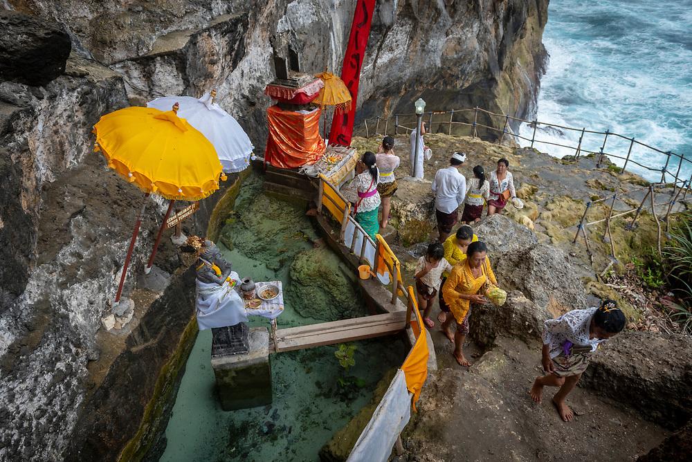 Nusa Penida, Indonesia - September 30, 2017: A Balinese family prays at a small seaside temple at Peguyangan Waterfall on Nusa Penida, an island located off the coast of Bali.