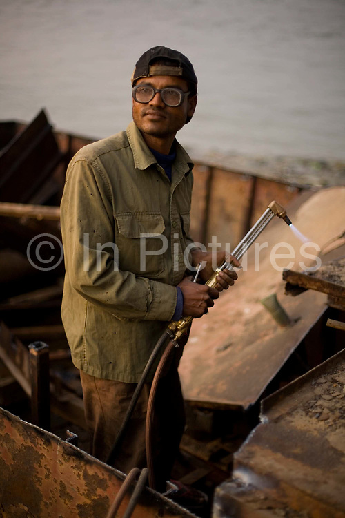 A man dismantles a boat with a blow torch and hammer on the banks of the Karnaphuli River beneath the Kalurghat Bridge, Chittagong, Bangladesh