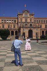 Plaza de Espana; Seville; with tourist taking photo of woman wearing traditional flamenco dress,