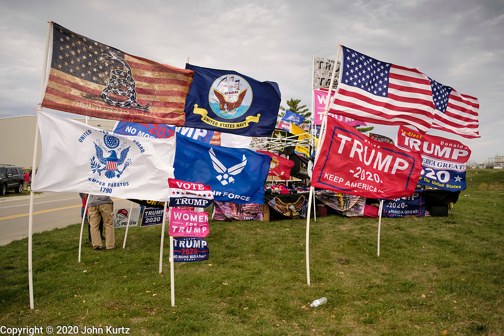 14 OCTOBER 2020 - DES MOINES, IOWA: Donald Trump and American flags for sale at a Trump reelection rally. About10,000 people were expected at the Des Moines International Airport for a campaign rally supporting the reelection of President Donald Trump. Trump spoke at the rally, despite testing positive for COVID-19 less than three weeks ago. The rally did not meet the CDC guidelines for a safe gathering in the time of Coronavirus and violated Iowa's health emergency declarations barring gatherings of more than 25 people. This week Iowa exceeded 101,000 cases of COVID-19 and a surge in hospitalizations for COVID-19.       PHOTO BY JACK KURTZ