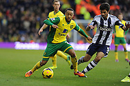 Norwich city's Nathan Redmond (l) goes past Claudio Yacob of WBA. Barclays Premier league, West Bromwich Albion v Norwich city at the Hawthorns in West Bromwich, England on Sat 7th Dec 2013. pic by Andrew Orchard, Andrew Orchard sports photography.