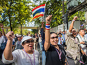 """29 NOVEMBER 2013 - BANGKOK, THAILAND: Anti-government chant """"Long Live the King!"""", as they march past the US Embassy in Bangkok. The protestors support the monarchy and are opposed the elected government. Several thousand Thai anti-government protestors marched on the US Embassy in Bangkok. They blew whistles and asked the US to honor their efforts to unseat the elected government of Yingluck Shinawatra. The anti-government protestors marched through several parts of Bangkok Friday paralyzing traffic but no clashes were reported, even after a group protestors tried to occupy Army headquarters.         PHOTO BY JACK KURTZ"""