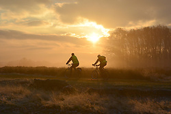 © Licensed to London News Pictures. 10/12/2013. Richmond, UK. Two men cycle along against the rising sun.  Sunrise and deer in Richmond Park, Surrey, this morning 10 December. Photo credit : Stephen Simpson/LNP