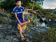 19 JUNE 2016 - DON KHONE, CHAMPASAK, LAOS: A fisherman sits on the shore at Khon Pa Soi Waterfalls, on the east side of Don Khon. It's the smaller of the two waterfalls in Don Khon. Fishermen have constructed an elaborate system of rope bridges over the falls they use to get to the fish traps they set. Fishermen in the area are contending with lower yields and smaller fish, threatening their way of life. The Mekong River is one of the most biodiverse and productive rivers on Earth. It is a global hotspot for freshwater fishes: over 1,000 species have been recorded there, second only to the Amazon. The Mekong River is also the most productive inland fishery in the world. The total harvest of fish from the Mekong is approximately 2.5 million metric tons per year. By some estimates the harvest in the Tonle Sap (in Cambodia) had doubled from 1940 to 1995, but the number of people fishing the in the lake has quadrupled, so the harvest per person is cut in half. There is evidence of over fishing in the Mekong - populations of large fish have shrunk and fishermen are bringing in smaller and smaller fish.     PHOTO BY JACK KURTZ