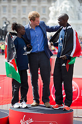 © London News Pictures. 22/04/2012. London, UK. HRH Prince Harry on the winner podium with Wilson Kipsang (right) and Mary Keitany of Kenya (left), the winners of the elite races at the 2012 Virgin London Marathon on April 22, 2012. Photo credit : Ben Cawthra /LNP