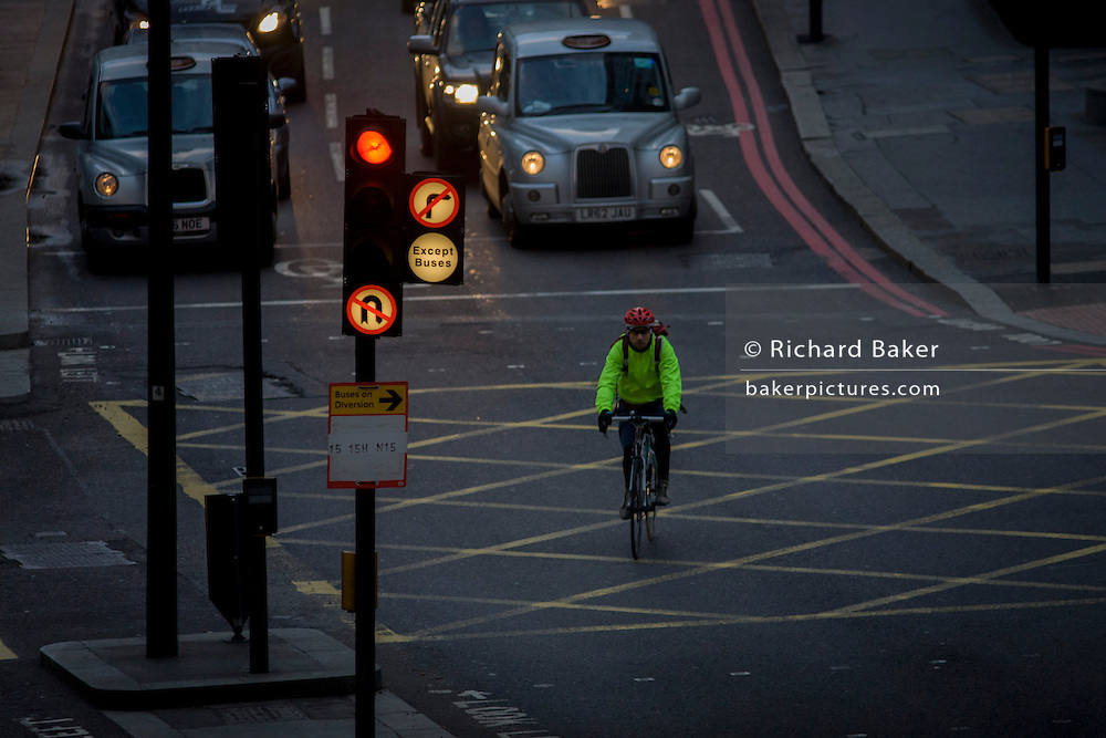 A cyclist crosses a box junction on a red light, at a crossing in the City of London.