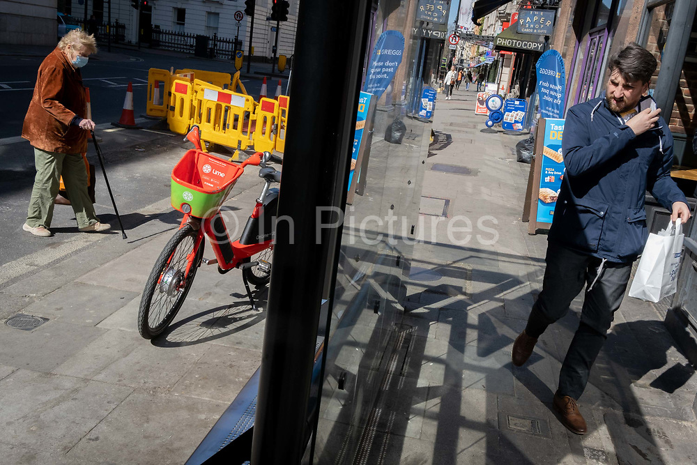 A discarded Lime rental bike stands in a bus shelter as an elderly woman crosses the road during the third lockdown of the Coronavirus pandemic, on 29th March 2021, in London, England.