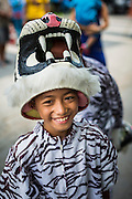 """05 JULY 2014 - BANGKOK, THAILAND: A child with a tiger outfit marches in a parade for vassa in Bangkok. Vassa, called """"phansa"""" in Thai, marks the beginning of the three months long Buddhist rains retreat when monks and novices stay in the temple for periods of intense meditation. Vassa officially starts July 11 but temples across Bangkok are holding events to mark the holiday all week.    PHOTO BY JACK KURTZ"""