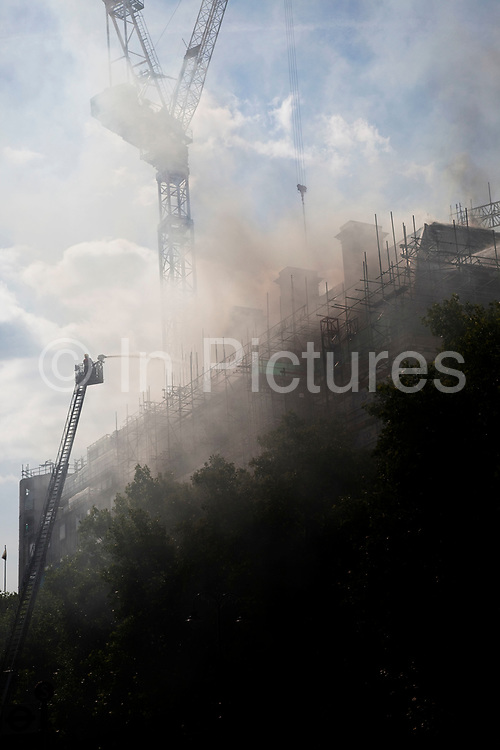 Fireman aims a jet of water at a large building on fire which was under refurbishment at Aldwych, in central London. Seventy-five firefighters are tackling the blaze on top of the building in London's West End, at the junction of the Strand and Aldwych. The fire took hold around 11am this morning in a 10-storey building which is currently being converted to a 5-star hotel and 86 luxury flats. Transport for London has closed areas nearby and has put in place diversions.