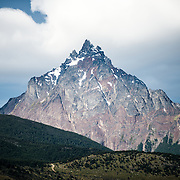 The distinctive, sharp triangle-shaped mountain is Monte Olivia (Mount Olivia).