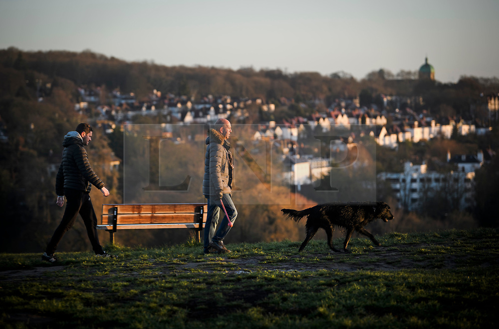 © Licensed to London News Pictures. 16/12/2018. London, UK. Dog walkers at sunrise at Parliament hill on Hampstead Heath, on a cold winter morning.  Large parts of the UK have experienced snowfall as storm Deidre brings freezing temperatures. Photo credit: Ben Cawthra/LNP