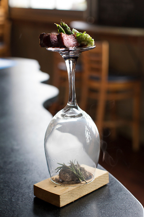 Ribeye is served on the bottom of a wine glass as rosemary burns on charcoal under the bell, the scent subtly escaping and rising upwards, at Travail and the Rookery in Robbinsdale April 18, 2014.