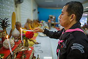 31 OCTOBER 2012 - YARANG, PATTANI, THAILAND:  A Thai army officer prays in Wat Kohwai before accompanying villagers in a procession to Yala for Ok Phansa. Ok Phansa marks the end of the Buddhist 'Lent' and falls on the full moon of the eleventh lunar month (October). It's a day of joyful celebration and merit-making. For the members of Wat Kohwai, in Yarang District of Pattani, it was a even more special because it was the first time in eight years they've been able to celebrate Ok Phansa. The Buddhist community is surrounded by Muslim villages and it's been too dangerous to hold the boisterous celebration because of the Muslim insurgency that is very active in this area. This the year the Thai army sent a special group of soldiers to secure the village and accompany the villagers on their procession to Yala, a city  about 20 miles away.  PHOTO BY JACK KURTZ