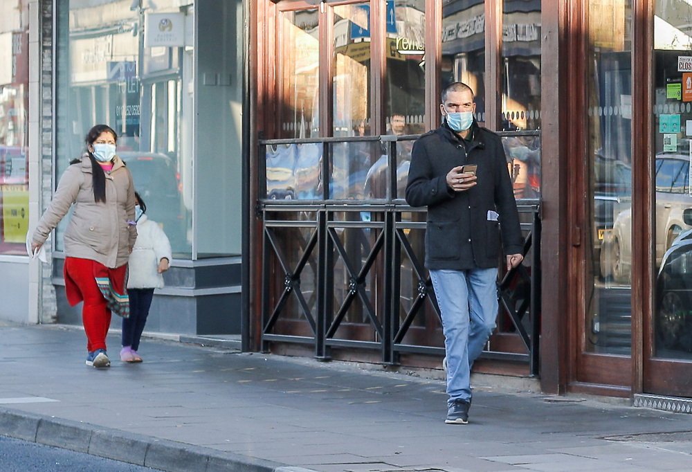 22nd February, Cheltenham, England. Mask wearers walk past a shop in Cheltenham Town centre during the third national lockdown.