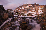 Water cascades down over rocks at the outlet of a lake in an alpine basin used as base camp for climbs of Glacier Peak in Glacier Peak Wilderness, Washington.