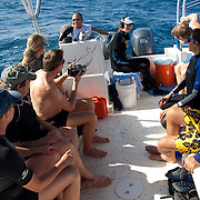 A group of whale watchers enjoy taking turns, using a hydrophone, listening to the sounds beneath the waters of the Caribbean Ocean.