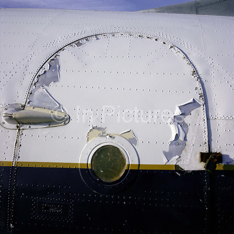 A detail of an ill-fated Comet airliner door now confined to the ground at the Imperial War Museum at Duxford, England. Peeling paint and a make-shift padlock shows this museum piece's age and exposure to the outside elements. A year after entering commercial service the Comets began suffering problems, with three of them breaking up during mid-flight in well-publicised accidents. This was later found to be due to catastrophic metal fatigue, not well understood at the time, in the airframes. The Comet was withdrawn from service and extensively tested to discover the cause; the first incident had been incorrectly blamed on adverse weather.