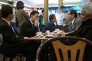 Japanese businessmen meeting up in coffee bar in Tokyo Japan