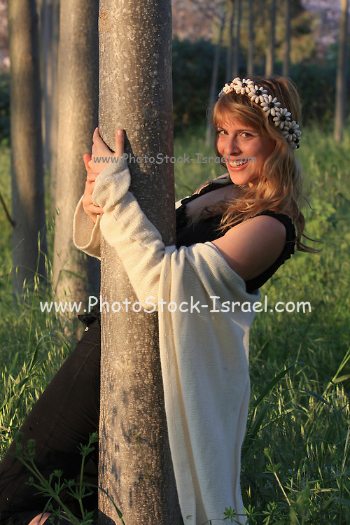 smiling young woman of 25 hugs a tree