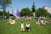 People gather on the grass in the sunshine at Jubillee Gardens on the South Bank in London, UK. The South Bank is a significant arts and entertainment district, and home to an endless list of activities for Londoners, visitors and tourists alike.