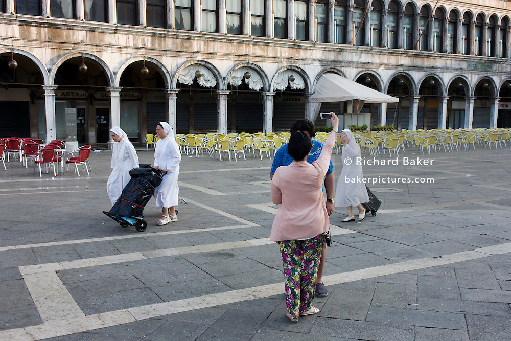 Nuns walk past selfie tourists in Piazza San Marco, Venice, Italy.