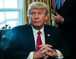 Washington, DC - February 3, 2017; U.S. President Donald Trump poses after signing an Executive Order in the Oval Office of the White House, to review the Dodd-Frank Wall Street to roll back financial regulations of the Obama era.