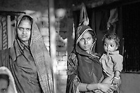 India, Varanasi, 1999. Late afternoon light bathes an extended family as they watch funeral preparations near the Ganges ghats.