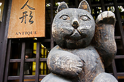 Detail of carved wooden cat outside traditional antique shop in historic town of Takayama in Japan