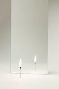 mirror with burning matchstick