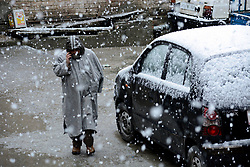 Kashmiri man walks amid  snowfall in Srinagar, the summer capital of Indian controlled Kashmir. Kashmir witnessed its first snowfall.