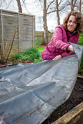 Covering a bed in the vegetable garden with black sheeting to warm the soil and prevent weeds