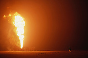 An oil well fire set by the Iraqi's in Kuwait after the end of the Gulf War in the Al Burgan field, March 1991. Larry Flak, the oil well fire coordinator, surveys the damage on one of the more than 700 wells set ablaze by retreating Iraqi troops in the largest man-made environmental disaster in history. A month after this photo was taken, the $20 billion effort to extinguish the fires began. Each day, in this oil field alone, the loss was estimated at 5 to 6 million barrels a day. This photo was made at mid-afternoon when the smoke from the fires made the desert as black as night. More than 700 wells were set ablaze by retreating Iraqi troops creating the largest man-made environmental disaster in history..Kuwait: Burning oil fields set by Iraqis. 10 am.