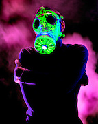 Man with glowing green gas mask stands in front of purple smoke.Black light