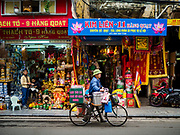 "22 DECEMBER 2017 - HANOI, VIETNAM: A hot drink seller pushes his bicycle through the old quarter of Hanoi. The old quarter is the heart of Hanoi, with narrow streets and lots of small shops but it's being ""gentrified"" because of tourism and some of the shops are being turned into hotels and cafes for tourists and wealthy Vietnamese.    PHOTO BY JACK KURTZ"