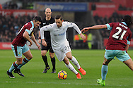 Swansea's Gylfi Sigurdsson (23) goes past Burnley's Joey Barton (r) and George Boyd (l). Premier league match, Swansea city v Burnley at the Liberty Stadium in Swansea, South Wales on Saturday 4th March 2017.<br /> pic by  Carl Robertson, Andrew Orchard sports photography.