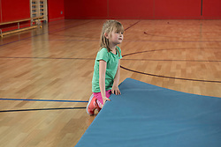 Girl trying to lift up heavy exercise mat in basketball court of sports hall, Munich, Bavaria, Germany