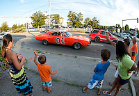 """Olivia Aubin, Zachary Haslam, Jacob Aubin and Renee Haslam wave as the """"General Lee"""" a 1969 Dodge Charger driven by David Fazio goes through downtown Meredith Saturday evening for the Cruise Night Parade.  (Karen Bobotas/for the Laconia Daily Sun)"""