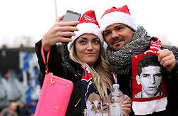 A pair of Arsenal fans wearing santa hats take a selfie outside the ground before the Premier League match at the Emirates Stadium, London.