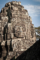 A huge smiling stone face at The Bayon temple in the walled city of Angkor Thom, Siem Reap, Cambodia