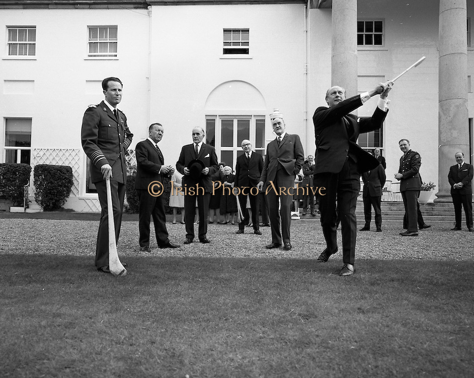 Having had a few lessons from All-Ireland winner Jack Lynch, King Baudouin takes a puck at the sliotar in the grounds of the Aras. Watching on are (l to r)Sean O Siochain, GAA President, Minister Frank Aiken, Presiden Eamon de Valera, and An Taoiseach Jack Lynch.<br /> 17.05.1968