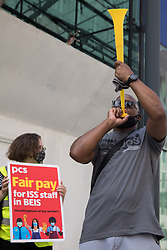 Members of the PCS trade union stand on the picket line outside the Department for Business, Energy and Industrial Strategy (BEIS) on the second day of a 3-day strike by workers employed there by outsourced contractor ISS on 20th July 2021 in London, United Kingdom. The striking cleaners, security guards and other support staff are demanding an end to low pay, improved working conditions, bonuses for having worked through lockdown, annual leave from last year and a Covid return-to-work protocol.