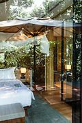Surrounding jungle reflected in villa bedroom floor-to-ceiling windows