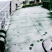 The bow deck of a ship in Antarctica in covered in a thin layer of fresh snow.