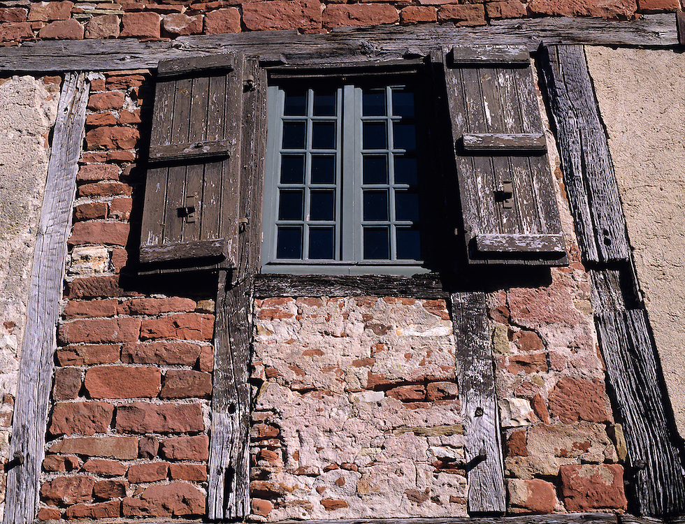 A shuttered-window fits into a half-timbered home in Collognes-la-Rouge in the Dordogne, France.