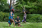 Traditional Mexican celebration of Mother's Day , Hackney , London, UK .May 13th 2012. Male drummer and female dancers with feather headdresses
