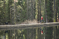 Young woman trail running along dam near Tahoe City, CA