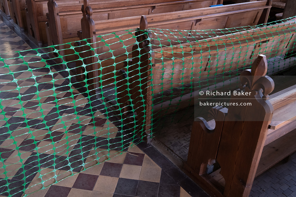 Green construction netting is stretched across the nave in Holy Trinity church in Ingham, a social distancing measure during the Coronavirus pandemic whose guidelines still allow the gathering of only single worshippers, on 10th August 2020, in Ingham, Norfolk, England.
