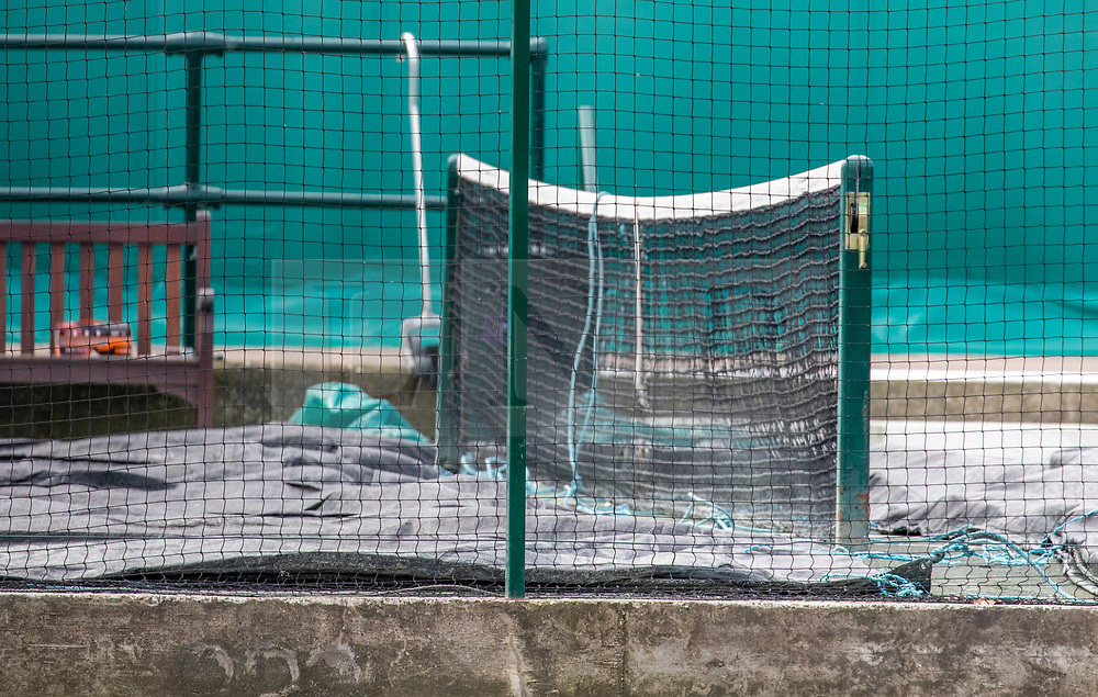 © Licensed to London News Pictures. 31/03/2020. London, UK. Tennis nets with crumpled protective sheeting at an empty looking All England Lawn Tennis Club, Wimbledon with no workers in sight. AELTC is set to announce on Wednesday (1 April) the cancellation of the Wimbledon Tennis Championships 2020 due to the coronavirus pandemic. The pandemic has led to the cancellation of major sporting events across the World as the coronavirus crisis continues. Photo credit: Alex Lentati/LNP