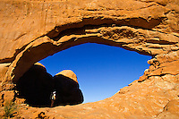 Hiker stands in the arch of The North Window, Arches National Park, Utah
