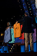 Aides bring several women's suits, presumed to be for Hillary Clinton on stage for a lighting and color check at Denver's Pepsi Center, site of the Democratic National Convention, Tuesday, Aug. 26, 2008. (Kevin Moloney for the New York Times)